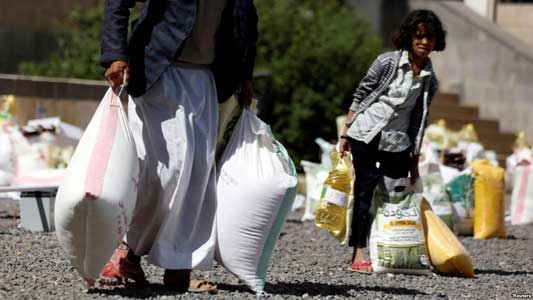 A young woman carries food received from a local charity during the holy month of Ramadan in Sanaa, Yemen, May 29, 2017.