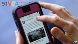 In this April 28, 2015, file photo, an Associated Press staffer poses using a mobile phone to read the news from The Huffington Post on Facebook, in Los Angeles. (AP Photo/Richard Vogel, File)