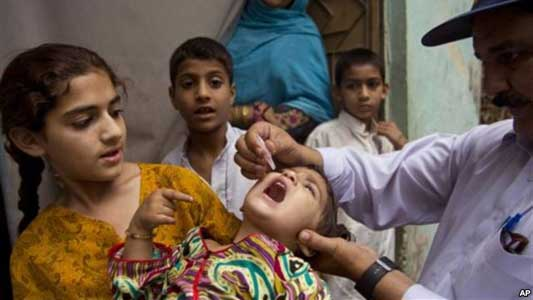 A Pakistani health worker gives a polio vaccine to a child in Rawalpindi, Pakistan, Tuesday, May 6, 2014.