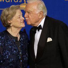 Legendary newscaster Walter Cronkite gives his wife Betsy a kiss as they pose for photographers at the 55th annual Primetime Emmy Awards