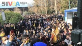 In this Saturday, Dec. 30, 2017 file photo taken by an individual not employed by the Associated Press and obtained by the AP outside Iran, university students attend a protest inside Tehran University while anti-riot Iranian police prevent them to