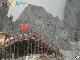 This Sept. 22, 2018 photo shows tourists visiting the Baishui Glacier No.1 atop of the Jade Dragon Snow Mountain in the southern province of Yunnan in China home. Scientists say the glacier is one of the fastest melting glaciers in the world due to climate cfhange and its relative proximity to the Equator. It has lost 60 percent of its mass and shrunk 250 meters since 1982. (AP Photo/Sam McNeil)