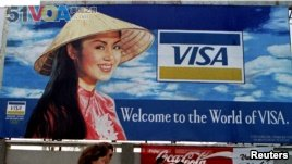 File - Two tourists walk past advertisements of foreign companies near the airport of Ho Chi Minh City. Vietnam hopes trade agreements will continue its economic growth.